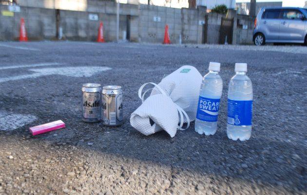 火災現場のビルと隣接する駐車場に置かれた花束や飲み物=18日、さいたま市大宮区