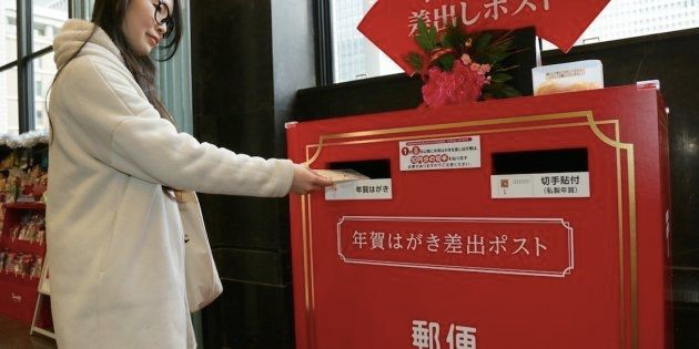 年賀状を投函する女性(イメージ画像)
