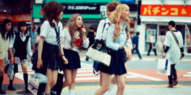 Japanese school girls with funky and crazy hair styles and mini skirts crossing the street in Shibuya,