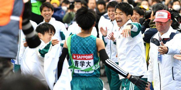 ゴールした10区の橋間(中央)を迎える青学大の選手ら=角野貴之撮影
