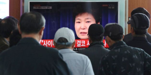People watch a TV screen showing the live broadcast of South Korean President Park Geun-hye's addressing...