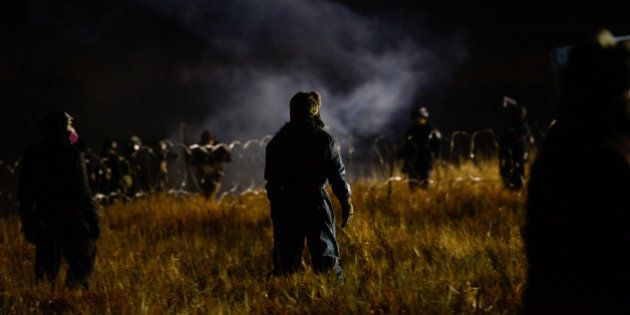 Protesters stand off with police during a protest against plans to pass the Dakota Access pipeline near...