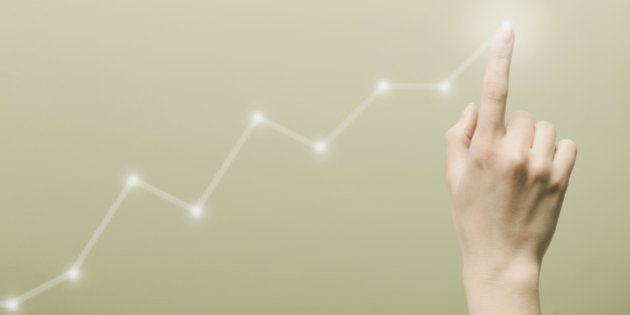 Woman's hand touching top of virtual chart graph with index