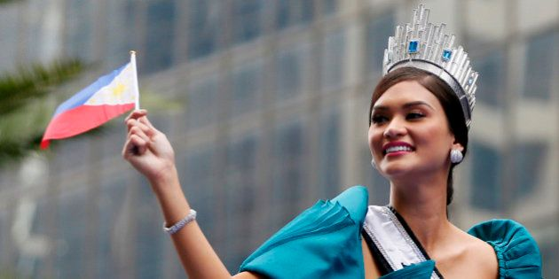 Newly crowned Miss Universe Pia Alonzo Wurtzbach waves a Philippine flag as her float passes by the financial...