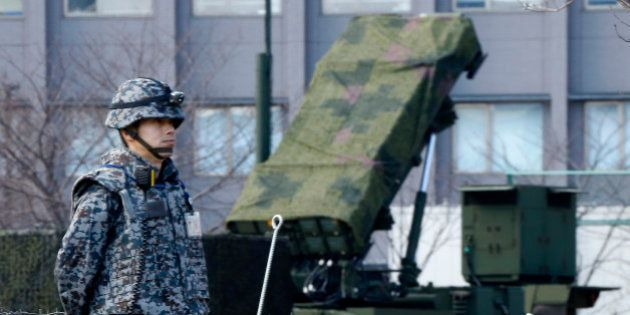 A Japan Self-Defense Force member stands by a PAC-3 Patriot missile unit deployed for North Korea's rocket...