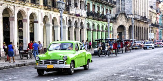 Street scene with vintage car and worn out buildings in Havana,