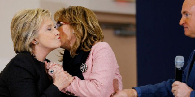Democratic presidential candidate Hillary Clinton embraces former Arizona Rep. Gabrielle Giffords, center,...