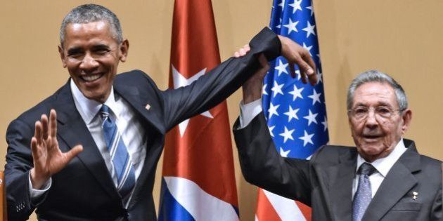 Cuban President Raul Castro (R) raises US President Barack Obama's hand during a meeting at the Revolution...