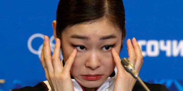 Yuna Kim of South Korea wipes her face as she attends a news conference following the women's free skate...