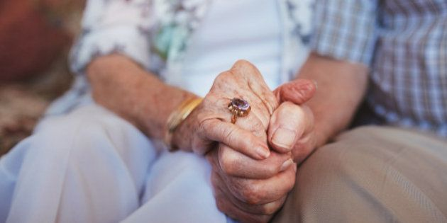 Cropped shot of elderly couple holding hands while sitting together at home. Focus on