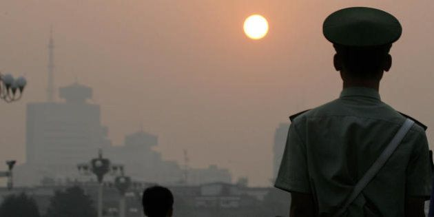 BEIJING, CHINA: A paramilitary policeman faces the sunrise while patrolling Tiananmen Square on a hazy...