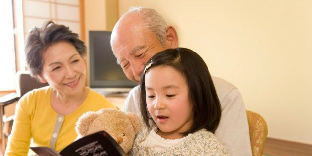 Girl with grandparents looking at brochure,