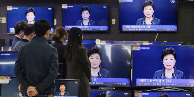 In this Friday, Nov. 4, 2016 photo, people watch TV screens showing the live broadcast of South Korean...