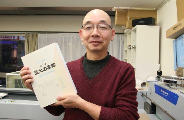 「2017年最大の素数」を手にする虹色社の山口和男さん
