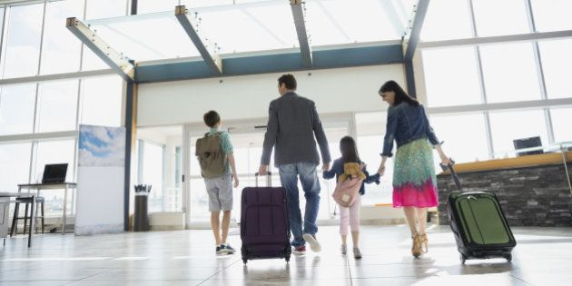Family with suitcases leaving