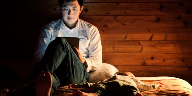 An asian father using a tablet pc on the bed at night, his baby boy sleeping by his