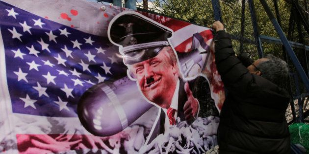 A demonstrator puts a banner with an image depicting U.S. President-elect Donald Trump as he takes part...