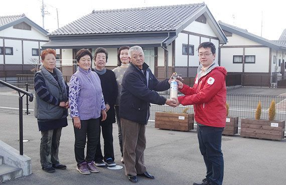 「消火器があると安心です」と受け取る相馬市の復興公営住宅にお住まいの皆さん。右はAARの櫻井佑樹(2018年1月10日)