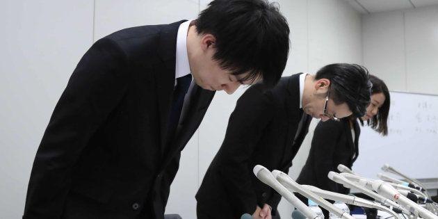 記者会見で頭を下げる仮想通貨取引所大手、コインチェックの和田晃一良社長(左)ら=26日夜、東京都中央区