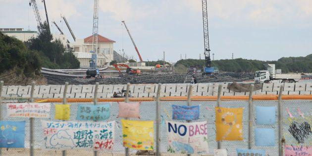 護岸工事が進む辺野古の沿岸部。米軍キャンプシュワブ境界線のフェンスには抗議の垂れ幕が掲げられている=沖縄県名護市