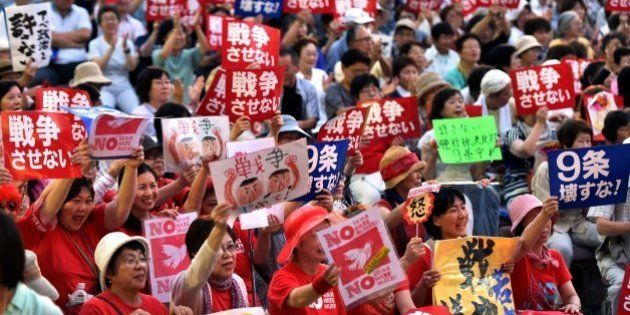 Civic group members hold placards and chant anti-government slogans in Tokyo on July 14, 2015 to protest...