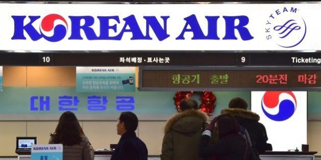 Travelers are seen at the Korean Air ticketing desk at Gimpo airport in Seoul on December 16, 2014. South...