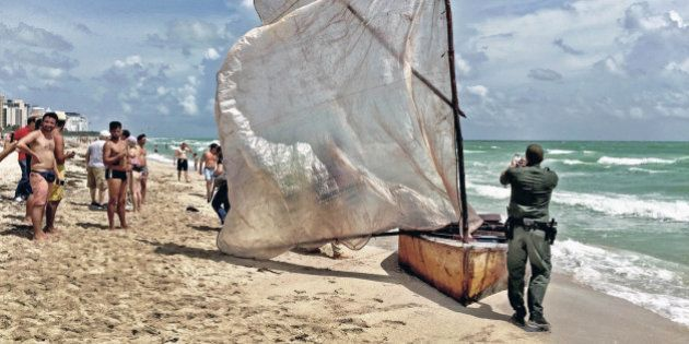 A U.S. Border Patrol agent photographs a boat with a makeshift sail that a group of Cuban migrants used...