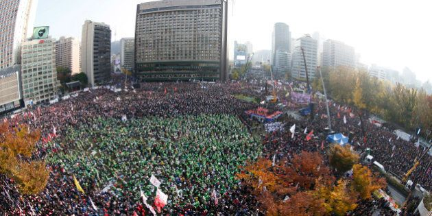 In this photo made with a fish-eye lens, South Korean people shout slogans during a protest against South...