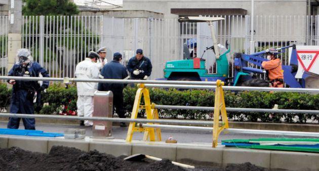 歩道に乗り上げた重機(奥)の周辺を調べる警察官ら=1日午後4時41分、大阪市生野区、広島敦史撮影