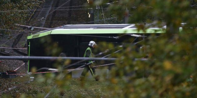 A member of the emergency services walks past a tram after it overturned injuring and trapping some passengers...