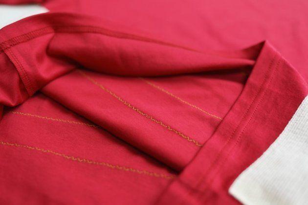 Tシャツの裏側に縫い付けてある黄色い糸を切って引き抜く