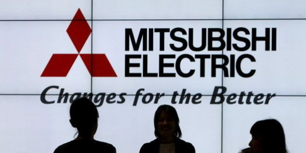 The company logo of Mitsubishi Electric is seen behind people at CEATEC (Combined Exhibition of Advanced...