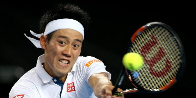 Kei Nishikori of Japan makes a backhand return to Jo-Wilfried Tsonga of France during their fourth round...