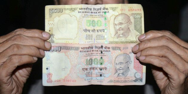 An Indian man holds 500 and 1000 INR notes in Amritsar on November 8, 2016. Indian Prime Minister Narendra...