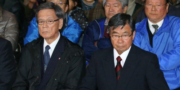 名護市長選挙で敗北が確実となり、厳しい表情の稲嶺進氏(右)。左は沖縄県の翁長雄志知事=4日夜、沖縄県名護市