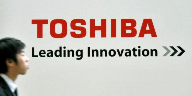 In this photo taken on Dec. 11, 2008, a man walks by a corporate logo of Japan's top chipmaker Toshiba...
