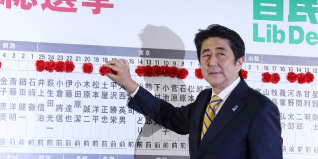 Shinzo Abe, Japan's prime minister and president of the Liberal Democratic Party (LDP), places a red...