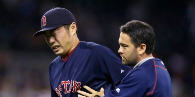 Boston Red Sox relief pitcher Koji Uehara is helped off the field after a baseball game against the Detroit...