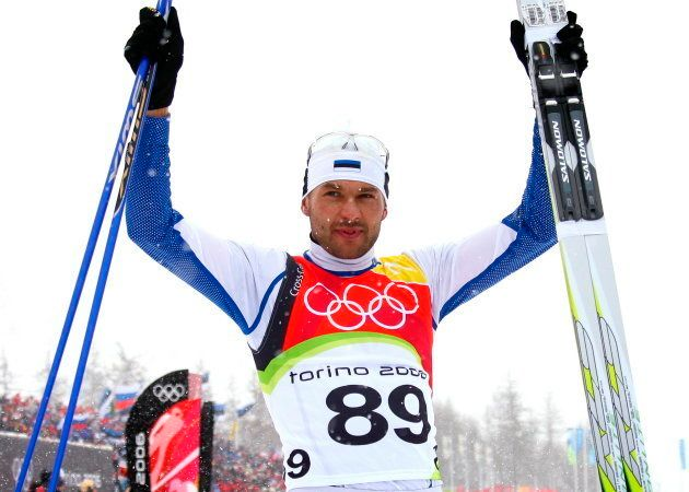 Estonia's Andrus Veerpalu raises his arms in jubilation after winning the men's 15km cross country skiing...