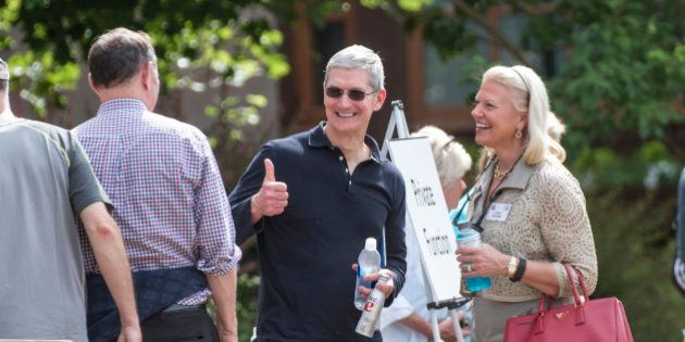Tim Cook, chief executive officer of Apple Inc., center, gestures to Donald Graham, former chairman and...