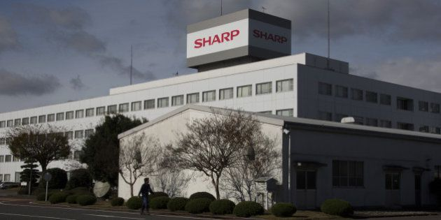 A man walks past the Sharp Corp. plant in Yaita, Tochigi Prefecture, Japan, on Thursday, Nov. 19, 2015....