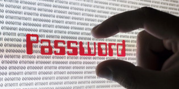 A male hand grabbing the word 'PASSWORD' on a computer screen with binary