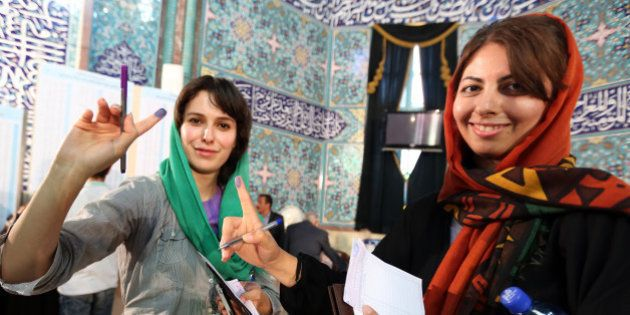 Iranian women display their ink-stained fingers as they cast their votes in the first round of the presidential...
