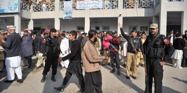Pakistani police and onlookers gather in front of a hospital following an attack by gunmen at Bacha Khan...