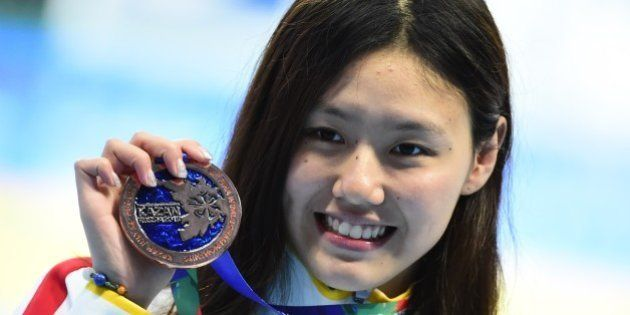 China's Liu Xiang poses with her bronze medal during the podium ceremony for the women's 50m backstroke...