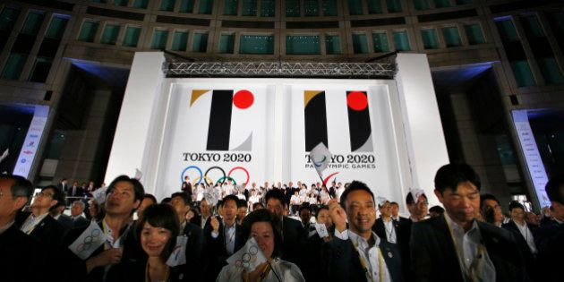 Visitors wave a flag for the Olympics and Paralympics in front of a official Emblems of the Tokyo 2020...