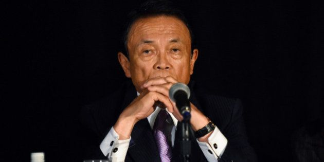 Japanese Finance Minister Taro Aso takes questions from reporters at the Willard Intercontinental hotel...