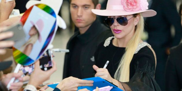 Lady Gaga gives her autographs to fans upon her arrival at Narita international airport in Narita, east...