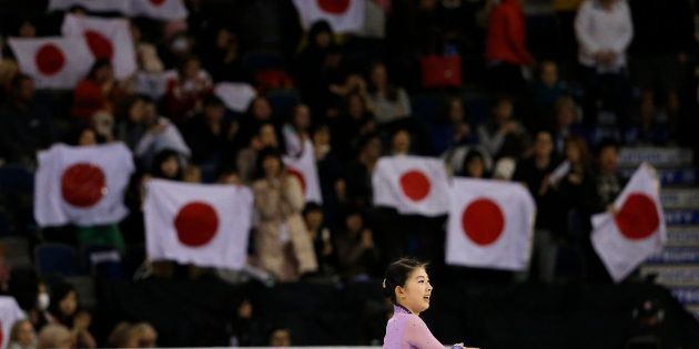 Fans wave Japanese flags as Yuka Nagai of Japan finishes her performance during the Ladies Short program...