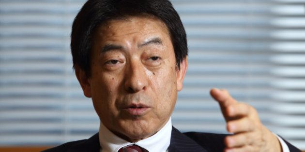 Yasuhisa Shiozaki, Japan's health, labor and welfare minister, gestures as he speaks during an interview...